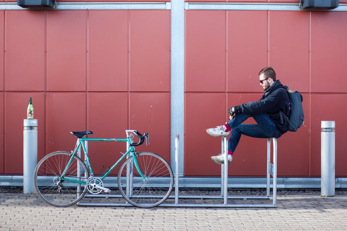 Man Sitting on White Bicycle Parking Space