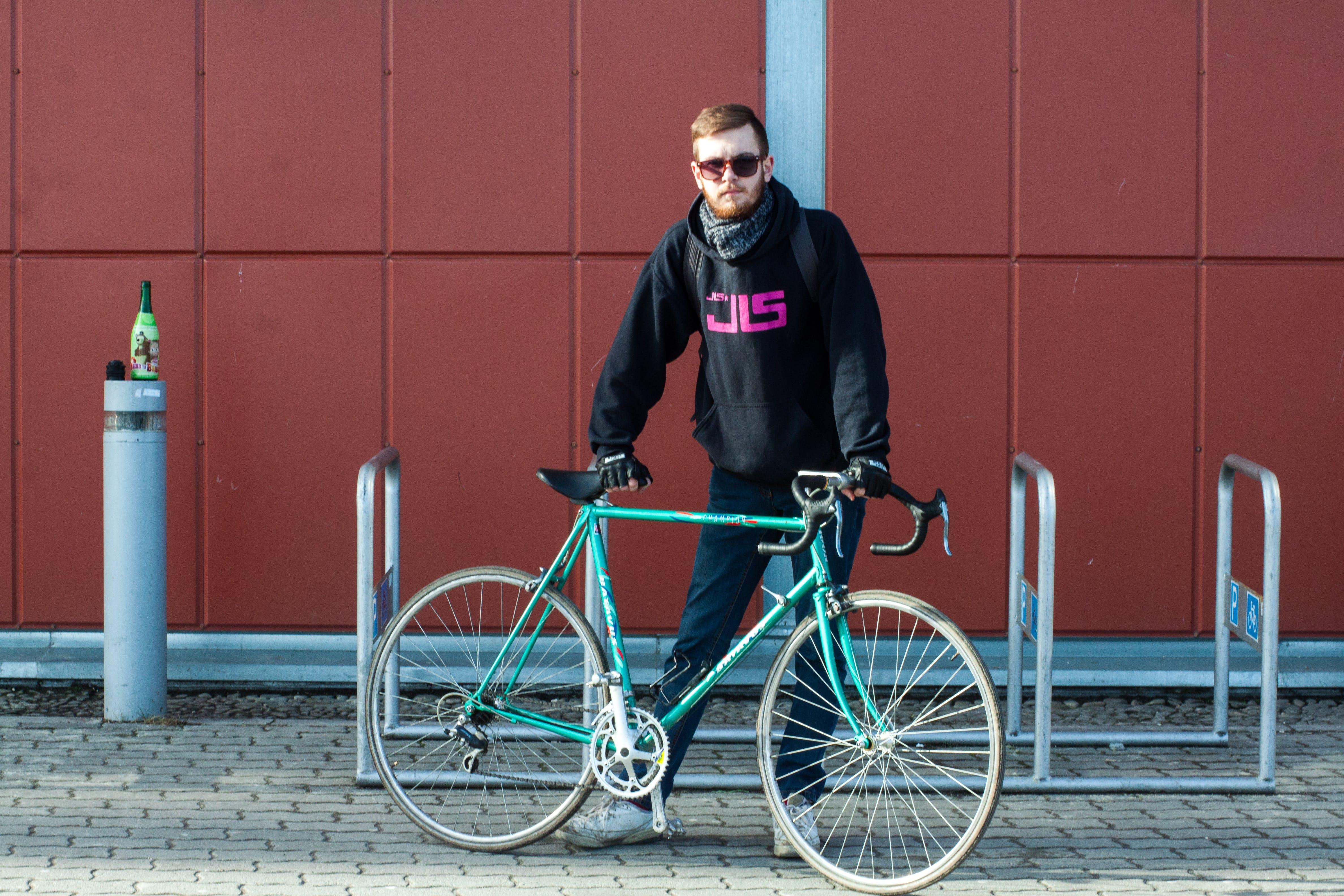 Person In Black Hoodie Holding Green Bike