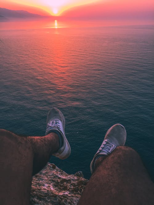 Man Sitting on Rock Cliff during Golden Hour