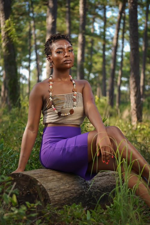 Woman Wearing Brown Top and Purple Skirt Sitting on Brown Log