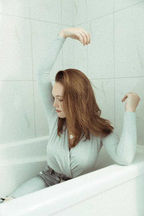 Woman in Gray Long-sleeved Shirt Sitting on Bathtub