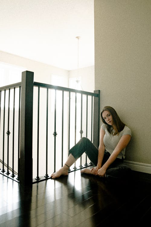 Photo of Woman Wearing White Blouse and Black Pants Sitting on Brown Wooden Plankboard Beside of Stair Rail