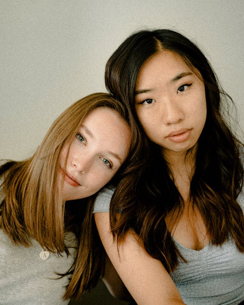 Woman Leaning on Woman's Shoulder Wearing Gray Top