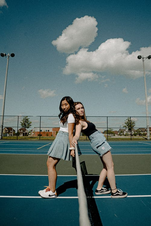 Photo of Woman Wearing White and Blue Dress Standing on Tennis Field With Girl Wearing Black Tank Top and Blue Denim Shorts