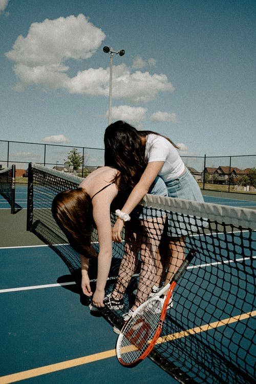 2 Women Besides Tennis Net