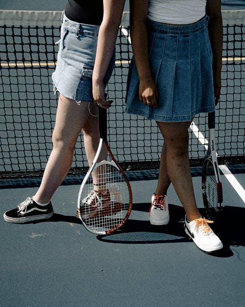 Two Women Holding Tennis Rackets