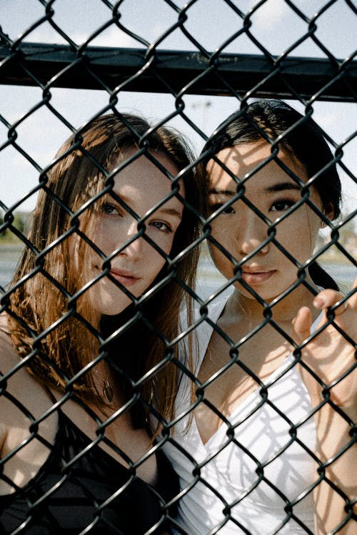 Two Women Standing Behind Chain-link Fence