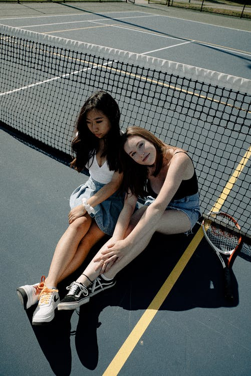 Photo Of Two Women Sitting on Tennis Court