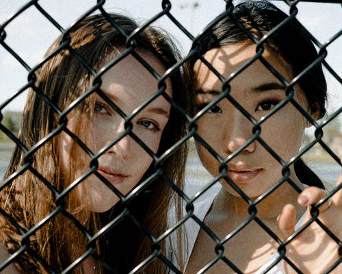 Two Women Leaning on Chain-link Fence