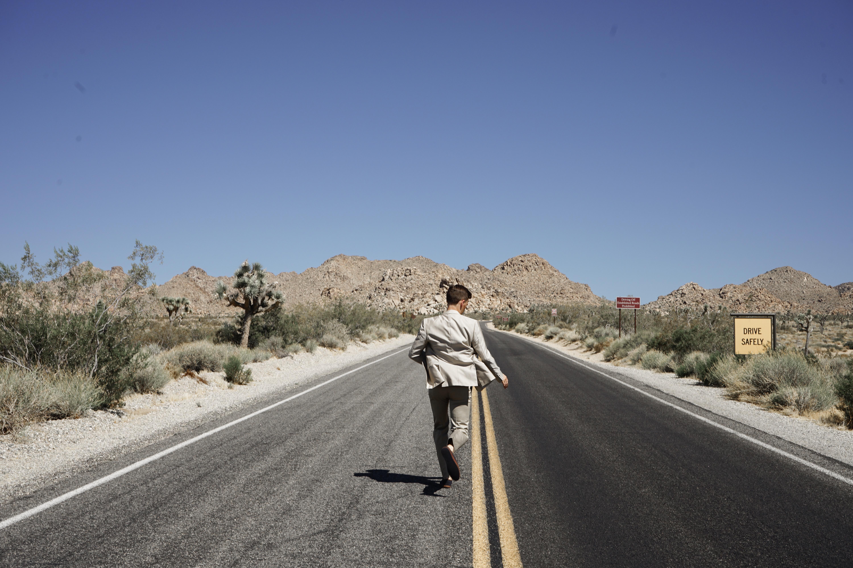 Man Wearing Gray Suit Jacket and Pants Running on Asphalt Road