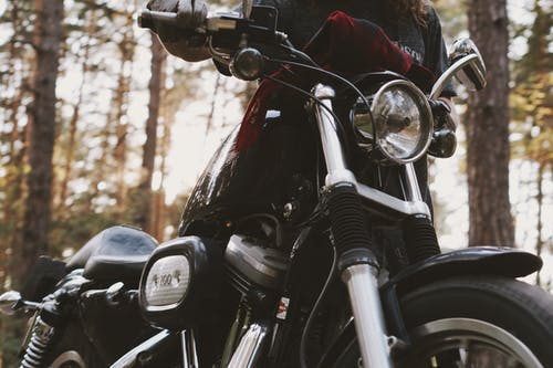 Close-up Photograph of Person Holding Black Motorcycle
