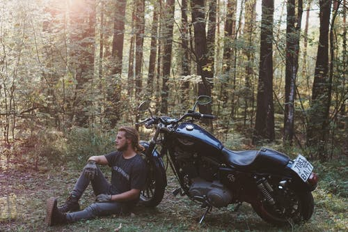 Man Sitting on the Ground Leaning Back on Parked Motorcycle