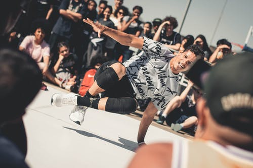 Man Wearing White and Black Shirt Break Dancing on White Surface