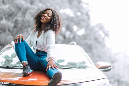 Free stock photo of car, curly hair, girl sitting on car