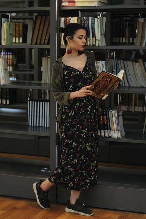 Woman Wearing Black and Red Floral Dress  Reading A Book