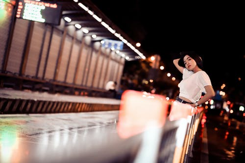 Photo of Woman Posing While Leaning on Railing at Night