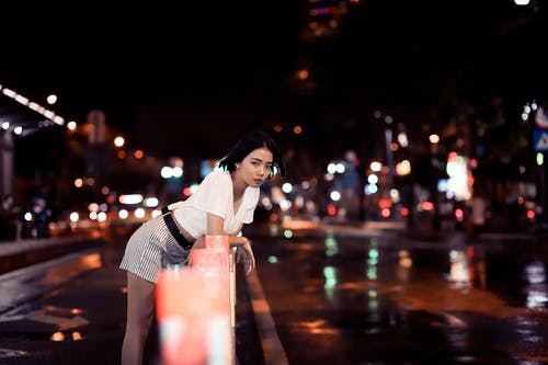 Woman Wearing White Top Leaning on Road Fence