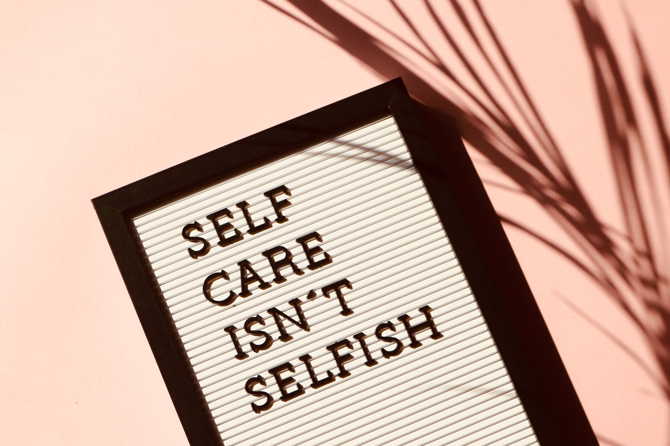 A picture of a sign that says 'Self-care isn't selfish'