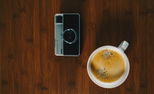 White Ceramic Mug Beside Black And Grey Camera