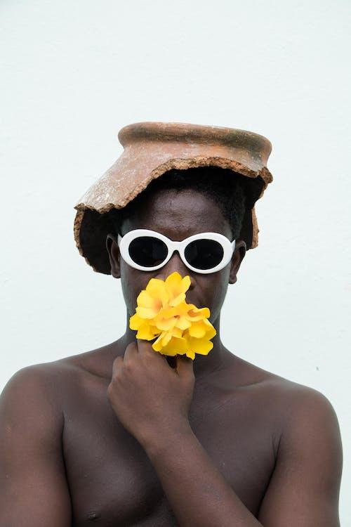 Kostnadsfri bild av afroamerikansk man, bar överkropp, blomkruka, blommor