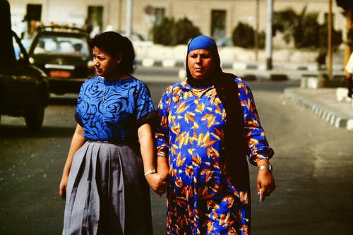 Photo of Two Women Walking While Holding Hands