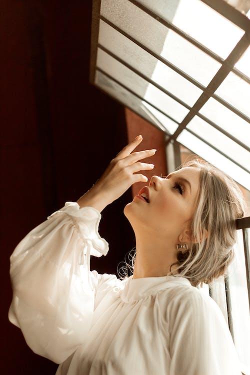 Mulher Vestindo Blusa Branca De Mangas Compridas Enquanto Olha Para Cima