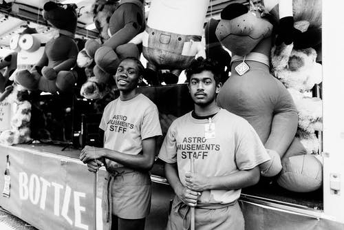 Two Astro Amusements Staffs Stand in Front Plush Toys
