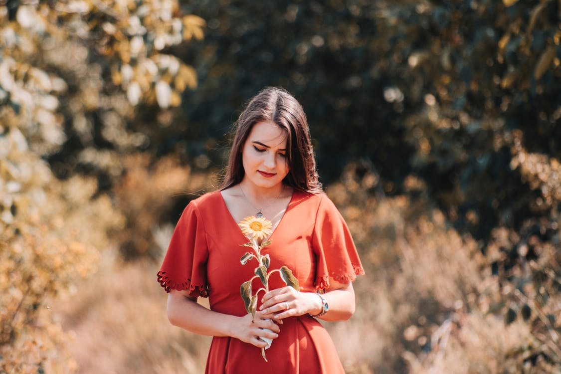 Woman Wearing Red Dress Holding Yellow Flower