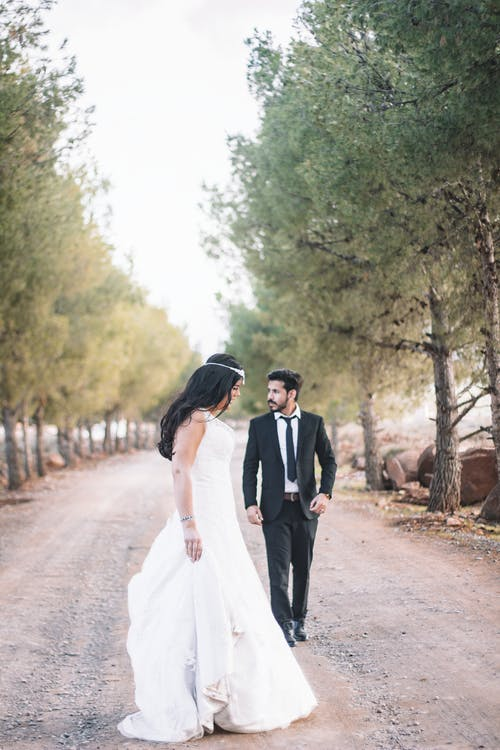 Newly Wed Couple Walking In Between Trees