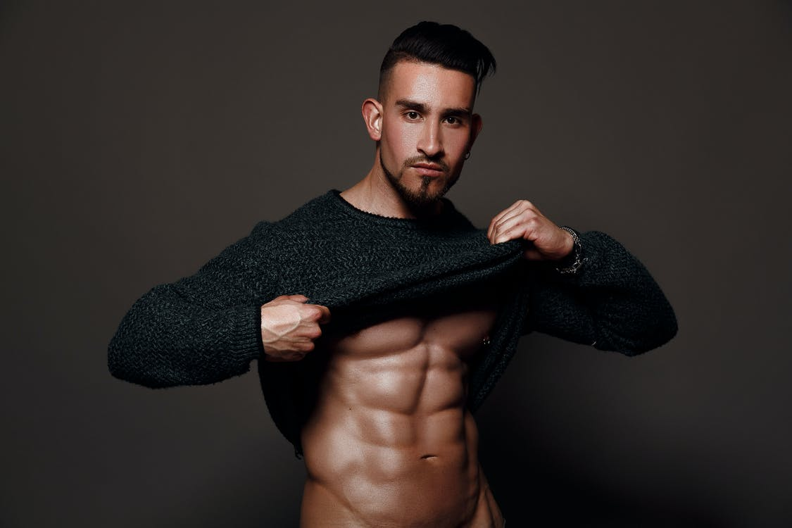 Muscular male with dark hair and beard standing against gray background and demonstrating torso by taking off sweater