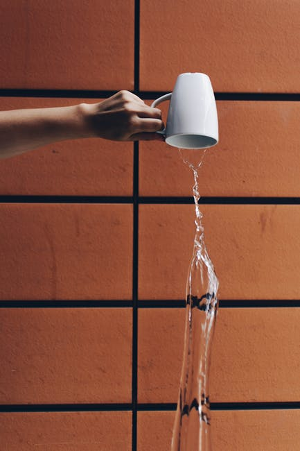 Person pouring water from cup
