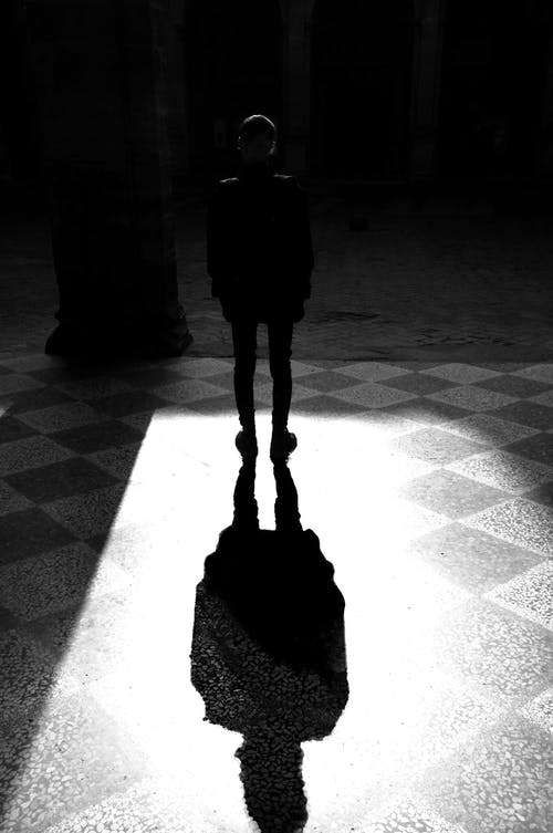 Grayscale Photography of Man Standing Under The Light