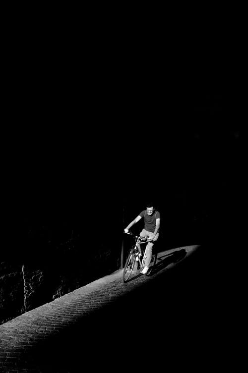 Grayscale Photo of Person Riding Bike