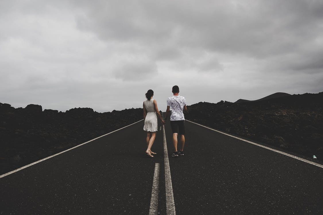 Photo Of Couple Holding Hands On The Road