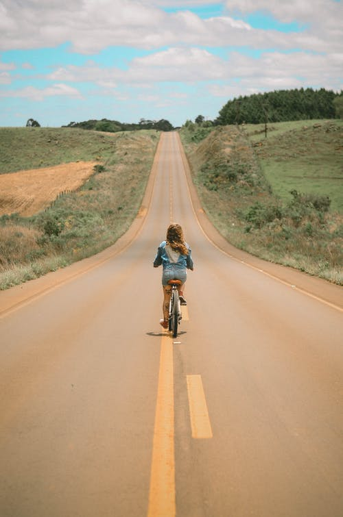 Girl Riding Bike in the Middle of the Road during Day