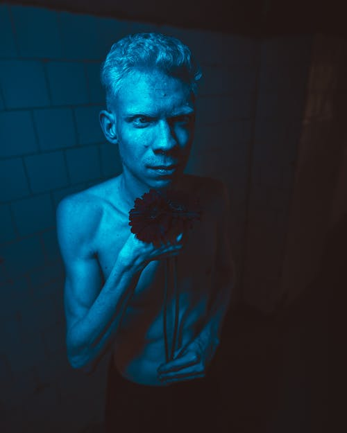 Topless Man Standing Inside Dimmed Blue Lighted Room
