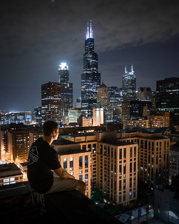 Man Sitting On Rooftop At Night