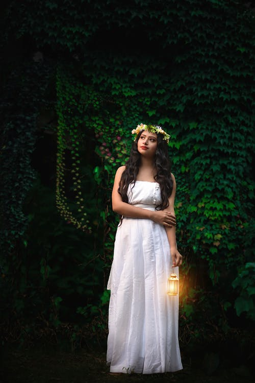 Photo of Woman in White Dress and Flower Crown Carrying Small Lantern while Standing Near Vine Plant