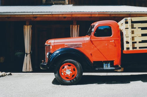 Orange Stake Truck Parked Beside Brown Building
