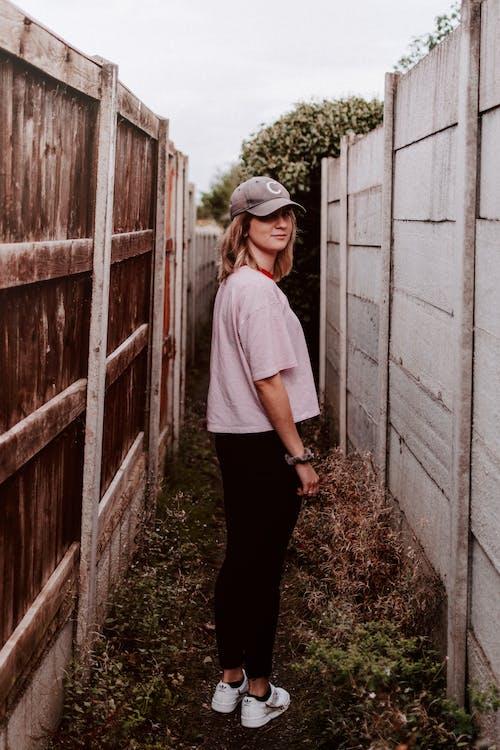 Woman Standing Between Fences