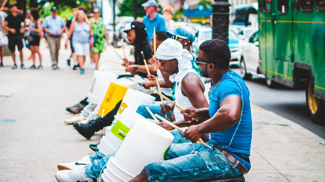 Group of Men Playing Drums Along The Street