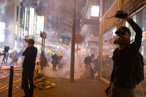 店の正面の横に立っているガスマスクを身に着けている男