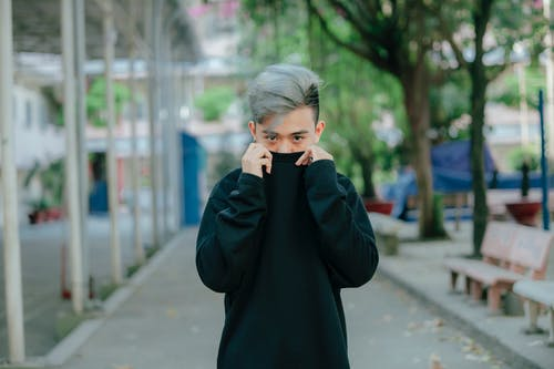 Selective Focus Photo of Man Posing While Covering His Mouth with a Black Sweater