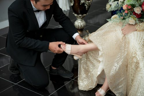 Man in Tuxedo Putting White Sandal on Sitting Woman