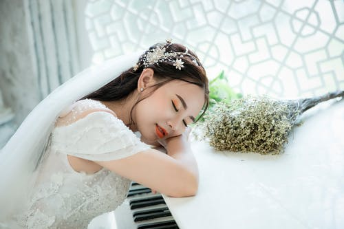 Photo Of Woman Taking A Nap On Top Of Piano