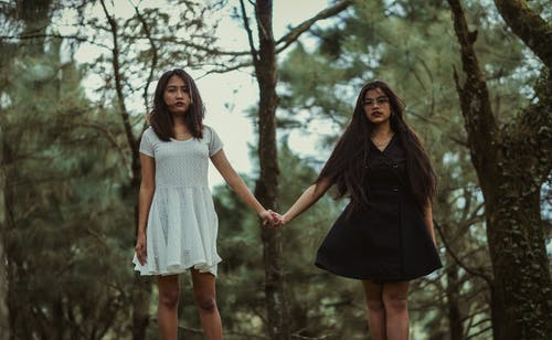 Girl Wearing White Dress Holding Hands With Girl Wearing Black Dress
