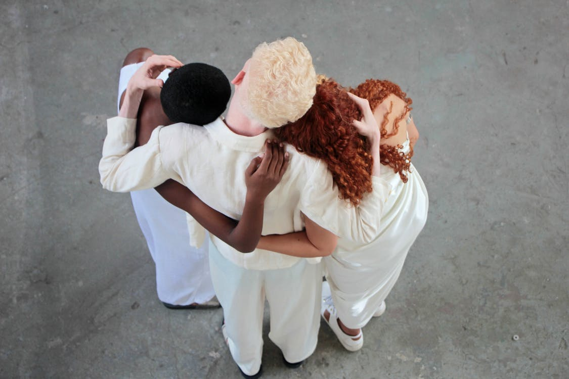 Back view of a Man Hugging Two Women