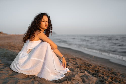 Woman Wearing a White Sleeveless Dress Sitting on the Beach Near a Body of Water