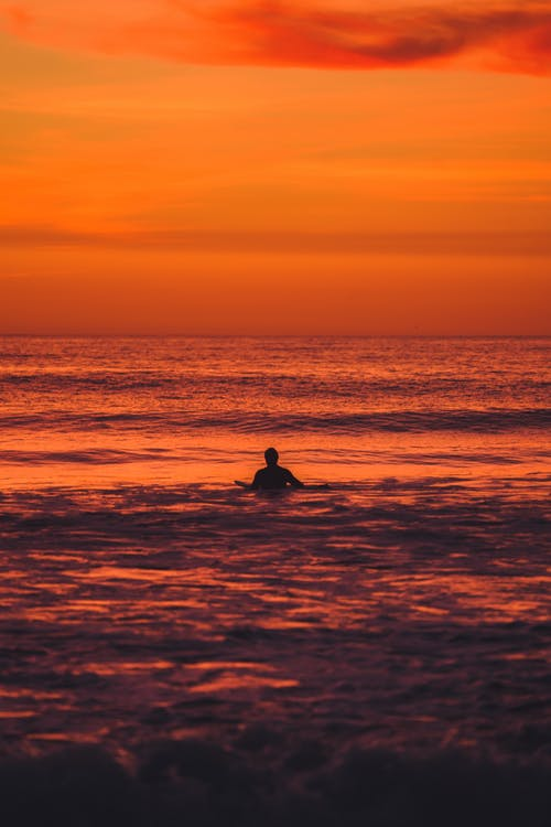 Person Swimming During Golden Hour