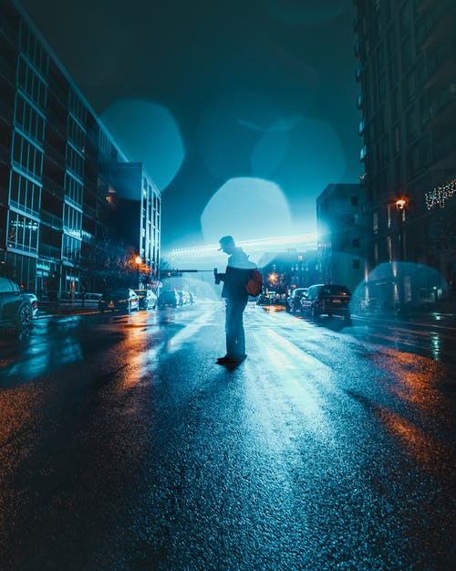 Person Standing on Road Between Buildings